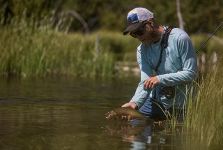 Frederik Lorentzen Fly Fishing Angler wears Fortis Eyewear releasing trout