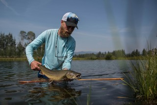 Frederik Lorentzen Fly Fishing Angler wears Fortis Eyewear releasing big brown trout